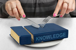 Consume knowledge concept, hands cut book on plate Royalty Free Stock Photos