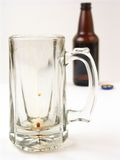Consumed. An empty, but recently used beer mug with a beer bottle in the background stock photo