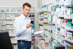 Consumer Checking Information On Mobile Phone In. Mid adult male consumer checking information on mobile phone while holding product in pharmacy Royalty Free Stock Images