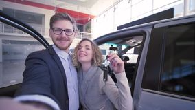 Consumer couple with keys take selfi photo on cell phone near new purchased vehicle in car dealership. Cheerful consumer couple with keys take selfi photo on stock video footage
