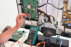 The consumer electronics repair engineer measures the voltage. On the television board Royalty Free Stock Photo