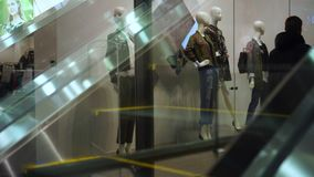 Consumer on escalators in shopping mall. People go on the escalator in trade mall. Reflection of legs of people on escalator glass. A show-window of shop from stock video