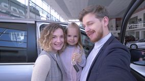 Consumer family with cute little daughter with keys take pictures phone on telephone near new purchased machine in car. Cheerful consumer family with cute little stock video