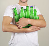 Consumer with a lot of bottles of beer. In their hands Stock Photography