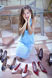 Consumer with shoes. Happy woman shopaholic with heap of shoes in shopping mall royalty free stock photos
