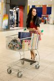 Consumerism. Girl with  handcart stand in mall Royalty Free Stock Image