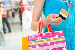 Consumerism. Close-up of woman�s hand holding plastic card while going shopping in the mall Stock Photo