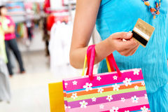 Consumerism. Close-up of woman�s hand holding plastic card while going shopping in the mall Royalty Free Stock Image