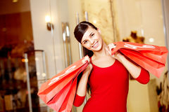 Consumerism. Happy girl holds red paperbags with symbol of sale and looking at camera Royalty Free Stock Photos