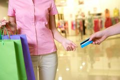 Consumerism. Close-up of woman taking plastic card from male hand in the mall Royalty Free Stock Images