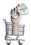 Consumerism. Manikin hand in a miniature shopping cart, holding money Stock Photos