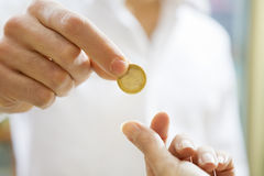 Consumerism. Man paying 1 euro to the cashier in a store. Close up of the coin and some copy space Royalty Free Stock Photos