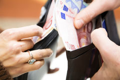 Consumerism. Young couple counting money in their wallet Royalty Free Stock Photo