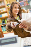 Consumerism. Woman doing shopping in a grocery store and paying by credit card Royalty Free Stock Photo