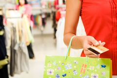 Consumerism. Close-up of woman�s hand holding plastic card while going shopping in the mall Stock Photography