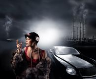 Consumerism. Portrait of a woman with fur, a luxury car and a factory Royalty Free Stock Images
