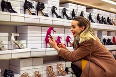 Consumerism, Christmas, shopping, lifestyle concept - happy women shopping at shoes store. Consumerism, Christmas, shopping, lifestyle concept - happy young royalty free stock images