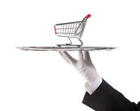 Consumerism concept. Waiter is having model of the shopping cart on tray stock image