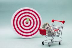 Consumerism concept. Shopping cart and target. On green background Royalty Free Stock Photo