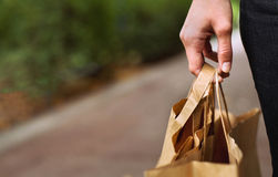 Consumerism concept. Shopping and retail, hand with bags, background Stock Image