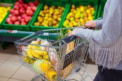 Consumerism concept. Woman doing grocery shopping at supermarket.  Royalty Free Stock Image