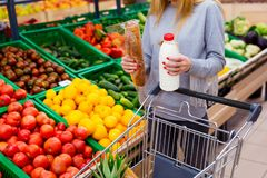 Consumerism concept. Woman doing grocery shopping at supermarket.  Stock Images
