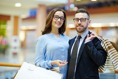 Consumerism. Couple of young customers visiting shopping-center Royalty Free Stock Photos