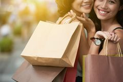 Consumerism. Cropped image of happy young Asian women with shopping bags Stock Photos