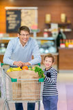 Consumerism. Dad and son with shopping cart Stock Photography