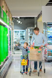 Consumerism. Dad and son with shopping cart Stock Photos