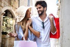 Consumerism förälskelse som daterar, loppbegrepp Lyckliga par som tycker om att shoppa ha gyckel arkivfoton
