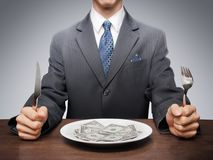 Consumerism. Greedy businessman eating banknotes symbolising consumerism Royalty Free Stock Photos