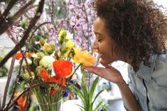 Consumerism: Kvinna som luktar nya blommor. Arkivbild