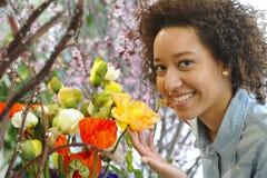 Consumerism: Kvinna som luktar nya blommor. Arkivfoton