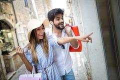 Consumerism, love, dating, travel concept. Happy couple enjoying shopping having fun. Consumerism, love, dating, travel concept. Beautiful couple enjoying royalty free stock photo