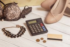 Consumerism and sale concept - calculator, women clothing, accessories. Consumerism and sale concept - calculator, women clothing, accessories Royalty Free Stock Images