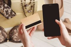 Consumerism and sale concept - close up of female hand with credit card and smartphone over women clothing, accessories.  royalty free stock photography