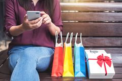Consumerism, shopping, lifestyle concept, Young woman sitting ne. Ar shopping bags and gift box while playing smartphone enjoying in shopping stock photography
