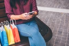 Consumerism, shopping, lifestyle concept, Young woman sitting near shopping bags and gift box while playing smartphone enjoying in royalty free stock image