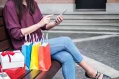 Consumerism, shopping, lifestyle concept, Young woman sitting near shopping bags and gift box while playing smartphone enjoying in. Shopping stock photos