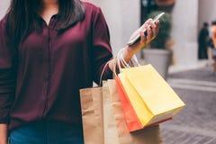 Consumerism, shopping, livsstilbegrepp, ung kvinna som rymmer färgrika shoppingpåsar, och smartphone som tycker om i shopping arkivfoto