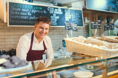 Consumerism. Smiling baker at the counter Royalty Free Stock Images