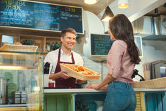 Consumerism. Smiling baker at the counter Royalty Free Stock Photography