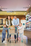 Consumerism. Smiling family with shopping cart Royalty Free Stock Photography