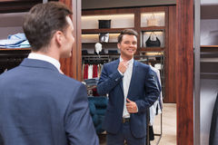 Consumerism. Smiling man with mirror in store Royalty Free Stock Image