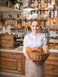 Consumerism. Smiling woman with basket of bread Stock Image