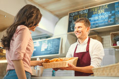 Consumerism. Young baker and customer in cafe Royalty Free Stock Image
