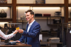 Consumerism. Young businessman with seller at checkout Stock Photo