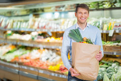 Consumerism. Young man with bag in store Stock Photos