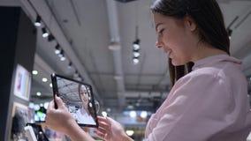 A consumição, comprador fêmea verifica a câmera e toma a foto do selfie no tablet pc moderno na loja da eletrônica vídeos de arquivo